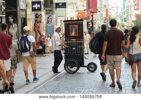 Athens, Greece - August 06 2016: A laterna (piano barrel) player at Ermou street. Laterna players used to walk the streets in past decades in return for money for the music they played.