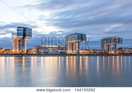 COLOGNE GERMANY - AUG 7 2016: The three Crane Houses at the Rhine river in Cologne illuminated at dusk. North Rhine-Westphalia Germany