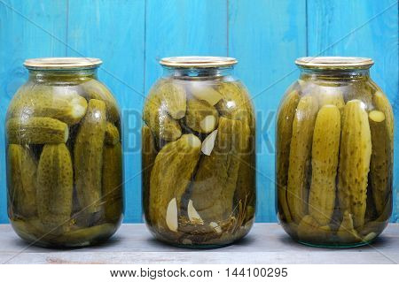 Three Jars Of Pickled Cucumbers On The Wooden Background
