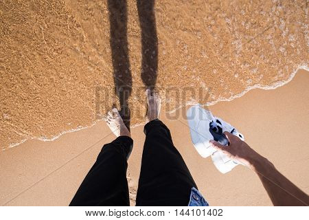 man wearing black jeans standing barefoot in the water holding white shoes