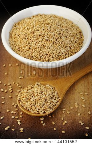 roasted sesame grain seeds in wooden spoon
