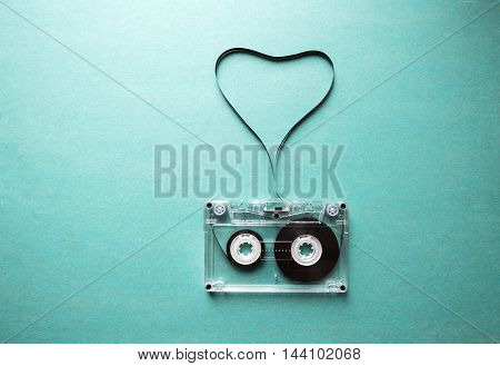 love to music, twisted audio tape in the shape of a heart on a green background