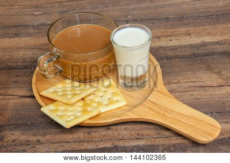 cup of coffee and a biscuit for breakfast  on wooden background