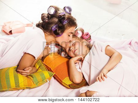 Little girl slipping with her mother in bed on white
