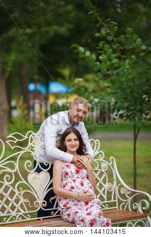 Young pregnant woman with husband sitting in the park