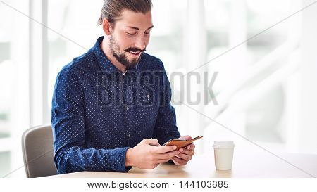 Handsome caucasian man with long hair tied in a bun busy messaging on his phone with a take away coffee on the table next to him in the cafe with copy space to the right of the image.