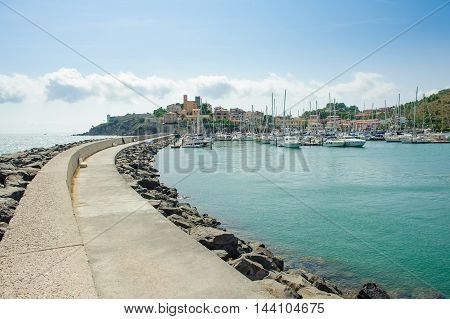 Talamone village Tuscany Italy. View from dock with many sailing boats in harbor and small town in background