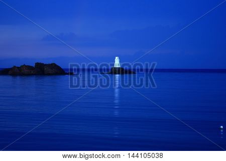 lighthouse at dusk on the rock in the sea