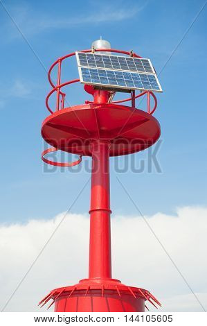 Red marine beacon light with solar panels energy close up on blue daylight sky
