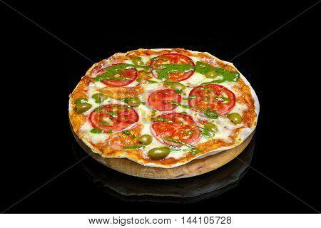Italian pizza Margherita with mozzarella olives tomato pesto sauce on a black background