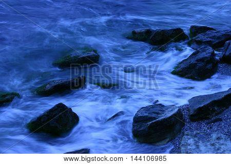blue waves crash into rocks at dusk