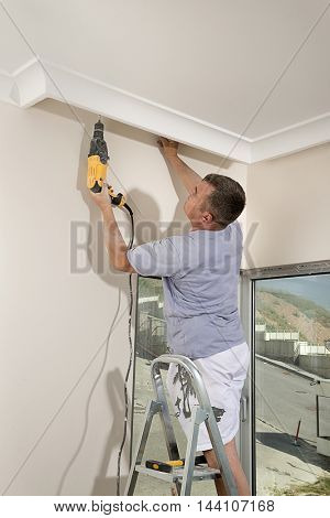 Manual worker drilling ceiling with a drilling machine.