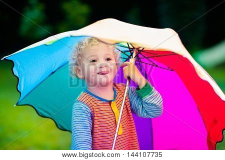 Little boy playing in rainy summer park. Child with colorful rainbow umbrella standing in the rain. Kid walking in autumn shower. Outdoor fun by any weather