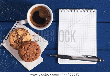 Notepad with empty page coffee cup and chocolate cookies on a dark blue table top view