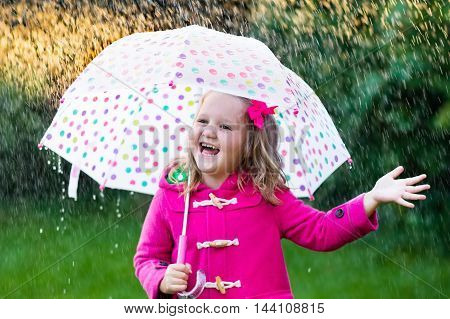 Little girl playing in rainy summer park. Child with colorful rainbow umbrella pink coat walking in the rain. Kid having fun in autumn shower. Outdoor activity by any weather