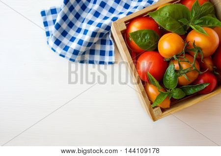 Red and yellow tomatoes and basil in box on a wooden background. Top view with copy space.