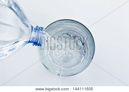 filling a glass with water through bottle on white background