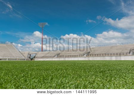 green filed gress of sport stadium with blue sky
