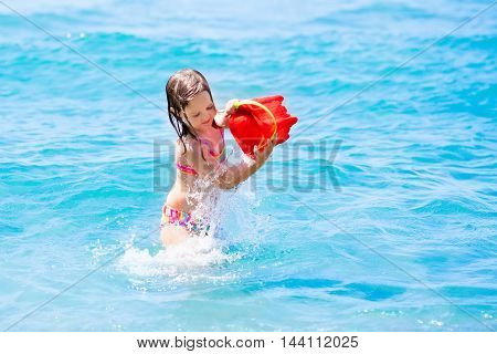 Little girl wearing colorful bathing suit playing on tropical ocean beach. Ocean fun for children. Toddler kid building sand castle during family sea vacation. Summer water activity.