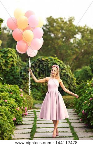 Beautiful young woman holding air balloons in garden