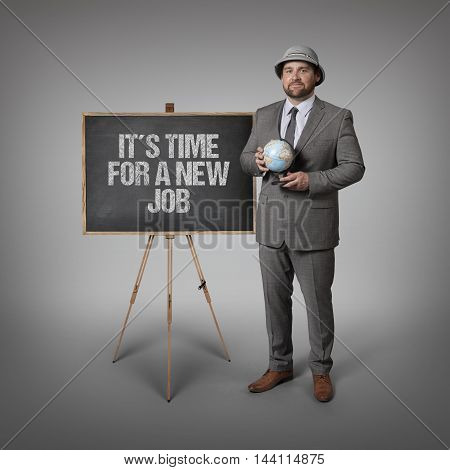 Its time for a new job text on blackboard with businessman holding globe in hands