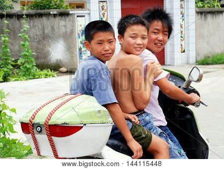 Pengzhou China - July 8 2007: Three Chinese boys riding on a motorcycle pass a Sichuan farmhouse