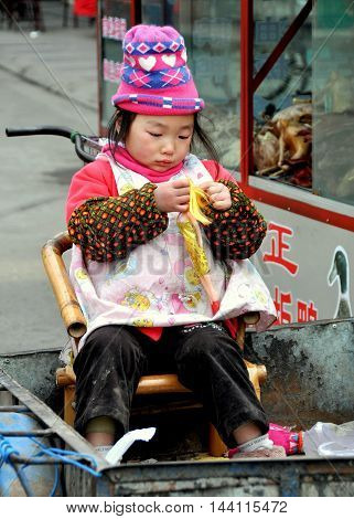 Pengzhou China - January 29 2011: Little Chinese girl sitting in a cart playing with a blond Barbie doll