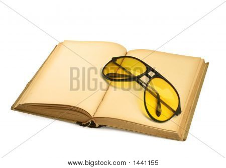Open Book With Yellow Sunglasses On White