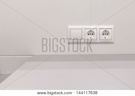 two electrical outlets and switch on the white wall