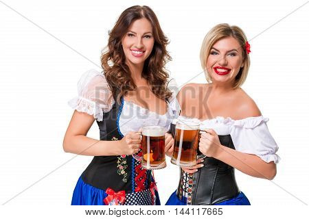 Two beautiful young blond and brunette girls in dirndl drinks out of oktoberfest beer stein. Isolated on white background.