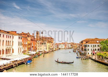 Venice, Italy - May 18, 2016: Cityscape view on Grand canal with Gondolier swim in gondola. Gondola is a traditional venetian boat and famous tourist attraction.