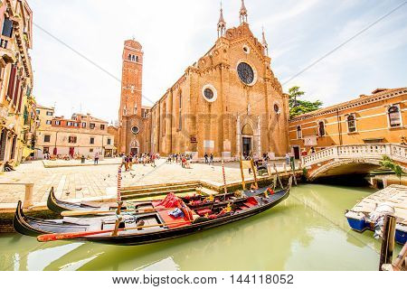 Venice, Italy - May 18, 2016: Cityscape view on canal with gondolas, crowded square and church dei Frari in Venice.