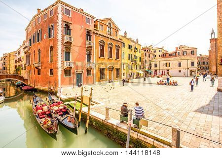 Venice, Italy - May 18, 2016: Cityscape view on canal with gondolas and crowded square dei Frari in Venice.