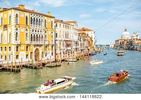 Venice, Italy - May 18, 2016: View on Grand canal full with water transports with Santa Maria basilica on the background from Accademic bridge in Venice