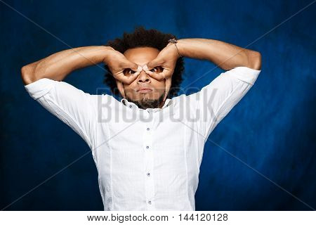 Young handsome african man in white shirt posing over blue background. Copy space.