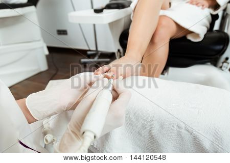 Portrait of young woman doing pedicure in salon. Beauty concept.
