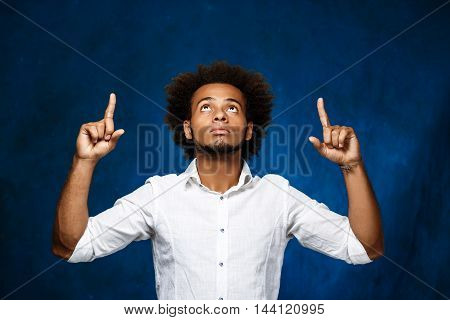 Young handsome african man in white shirt pointing fingers up over blue background. Copy space.