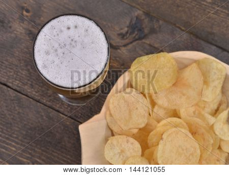 Beer glass near a gold salted potato chips in a wooden bowl on a rustic brown table, top view