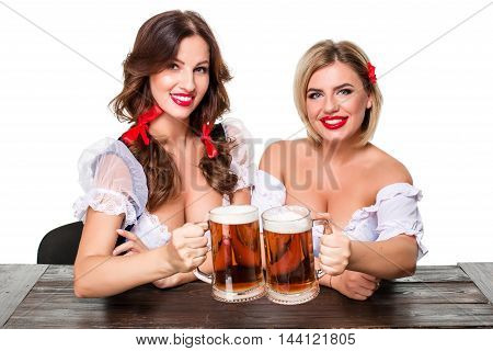 Two beautiful young blond and brunette girls in dirndl drinks out of oktoberfest beer stein. Isolated on white background. sits by the table