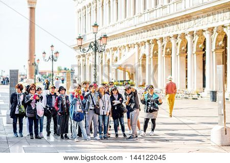 Venice, Italy - May 18, 2016: Group of asian tourists stand on San Marco square. Venice is very popular tourist destination among people from asia.