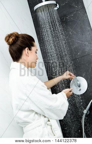 Portrait of woman's hands beneath shower of water.