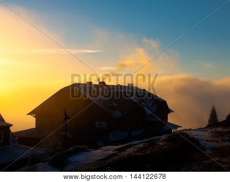 Dark silhouette of mountain hut at sunset time, Giant Mountains, Czech Republic