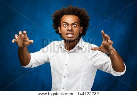 Young handsome african man in white shirt fooling over blue background. Copy space.