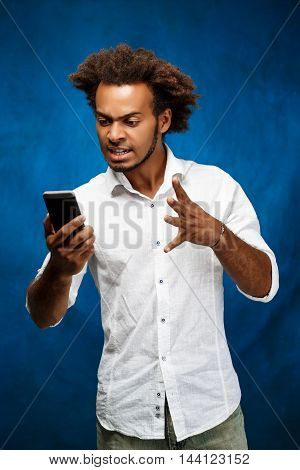 Angry young handsome african man in white shirt looking at phone over blue background. Copy space.