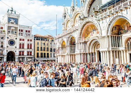 Venice, Italy - May 18, 2016: San Marco square near basilica and astronomical clock tower crowded with tourists. This square is the most popular place among tourists in Venice