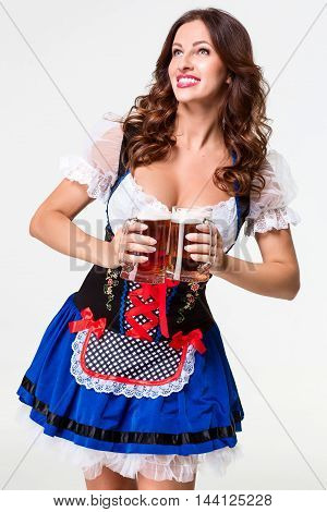 Beautiful young brunette girl in dirndl drinks out of oktoberfest beer stein. on white background.