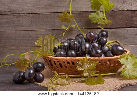 Blue grapes in a wicker basket on wooden table.