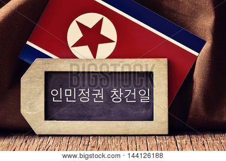 the text Day of the Foundation of the Republic written in Korean in a label-shaped chalkboard, and a flag of North Korea, on a rustic wooden surface