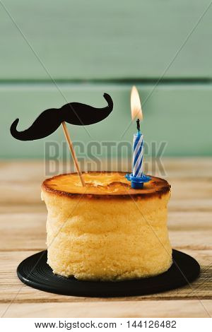 a cheesecake topped with a moustache attached to a stick and a lit birthday candle, on a rustic wooden surface against a pale green wooden background