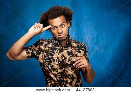 Young handsome african man posing, pointing finger at head over blue background. Copy space.